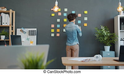 Creative person sticking bright sticky notes on wall in ...