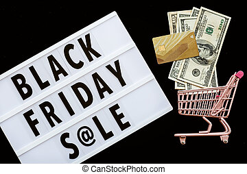 Creative promotion composition Black friday sale text on lightbox on black background, next grocery trolley, credit card, cash money. Flat lay, top view, overhead, mockup
