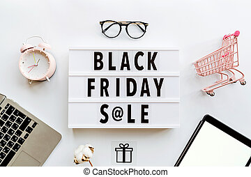 Creative promotion composition Black friday sale text on lightbox on white background, next grocery trolley, credit card, cash money, mobile phone, shopping bag. Flat lay, top view, overhead, mockup