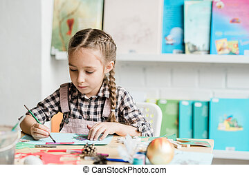 Creative schoolgirl with paintbrush sitting by desk and drawing xmas picture