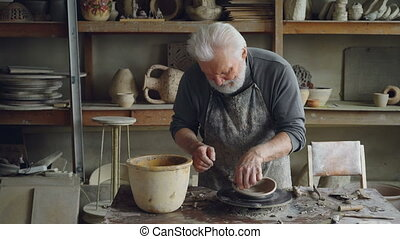 Creative sculptor is making unusual broad bowl while...