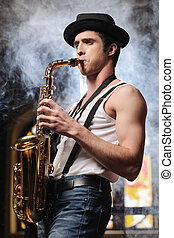 Creative soul. Handsome young man in hat playing sax with a...