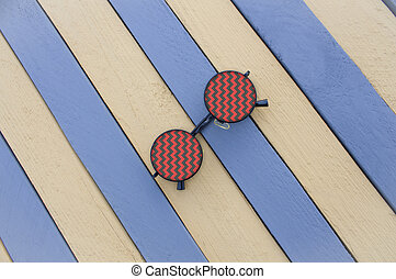 Creative sunglasses on a striped surface