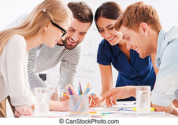 Creative team at work. Four cheerful business people in smart casual wear discussing something while leaning at the table
