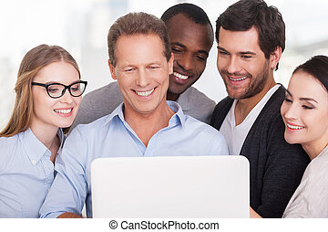Creative team at work. Group of business people in casual wear standing close to each other and looking at the laptop