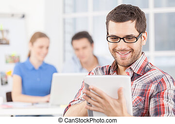Creative team. Cheerful young man in glasses using digital...