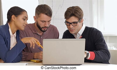 Creative team of two men and one woman sitting at the office