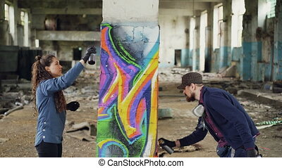 Creative team of two urban painters are drawing graffiti with spray paint while decorating old industrial warehouse with destroyed dirty walls and windows.