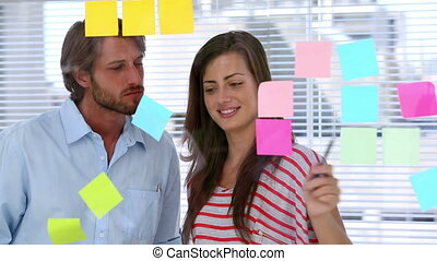Creative team pointing adhesive notes on transparent board