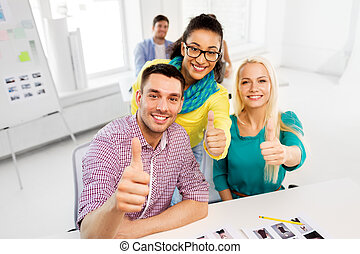 creative team showing thumbs up at office