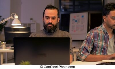 creative team with computer working late at office -...