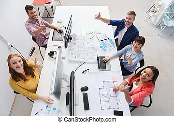 creative team with computers showing thumbs up