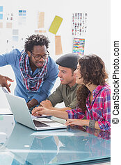 Creative team working together on laptop