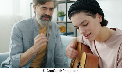 Creative teenager is playing the guitar while father is watching and teaching sharing experience at home. Family activities and musical instruments concept.