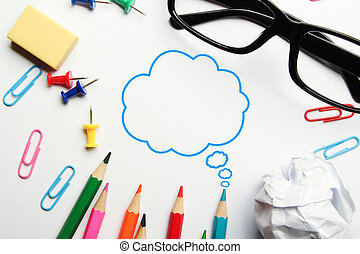 Creative thinking bubble concept with some office supplies around it on white background.