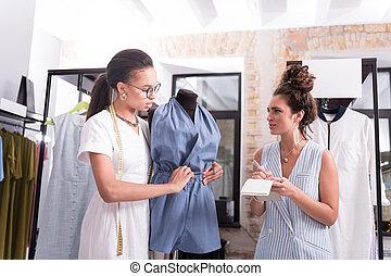 Creative two designers debating over overalls in showroom