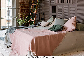 Creative use of small space in a stylish bedroom interior with designer decor and cozy white and beige bedding. Minimal loft style. Pastel soft colors. decorative ladder in interior