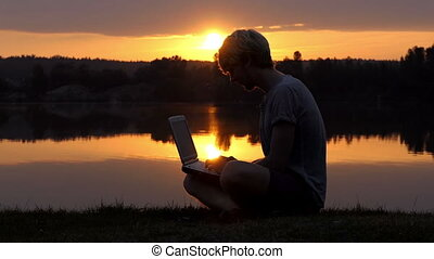 Creative Wan Types on His Laptop on a River Bank at a...