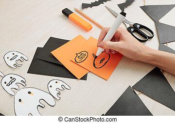 Creative woman drawing Halloween symbols