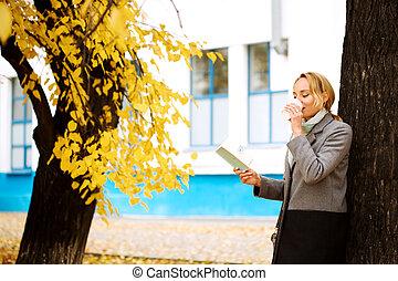 Creative woman in autumn park drinking take away coffee