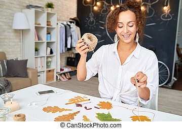 Creative Woman Making Autumn Leaves Decoration