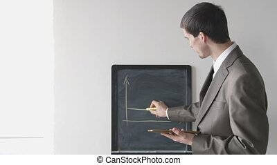Creative young businessman in suit draws chalk on board. 4k,...