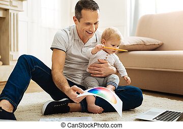 Creative young father entertaining his child and smiling cheerfully