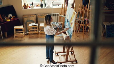 Creative young lady is busy painting picture working alone...