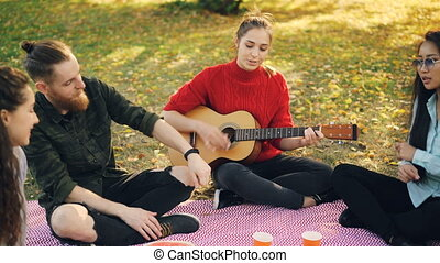 Creative young lady is playing the guitar while her male and...