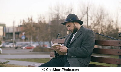 Creative young writer man in hat and coat write notes for his future book with pen in notebook sitting on city street bench at park