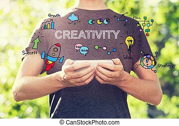 creativiteit, concept, met, jonge man, vasthouden, zijn, smartphone, buiten