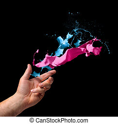 Creativity concept hand throwing paint on black background