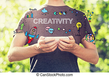 Creativity concept with young man holding his smartphone outside
