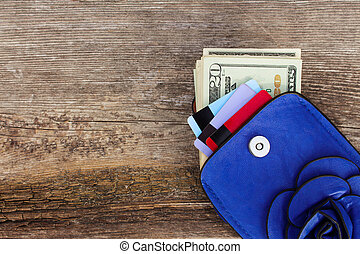 Credit card and dollars in wallet on wooden background. Top view.