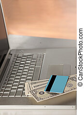 credit card and money on laptop