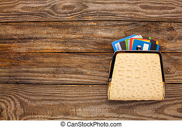 Credit card in wallet on wooden background. Top view.