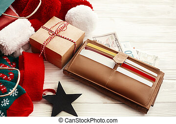 Credit cards and money in wallet, paper bags with clothes, stockings, gift boxes, jewelry on white rustic background. Black Friday sale. Christmas shopping and seasonal sale