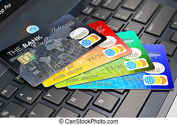 Credit cards on laptop keyboard - Creative abstract internet...
