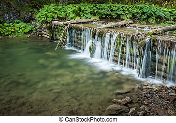 creek and man made waterfall in the forest