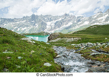 Creek flowing into the lake on a background of mountains
