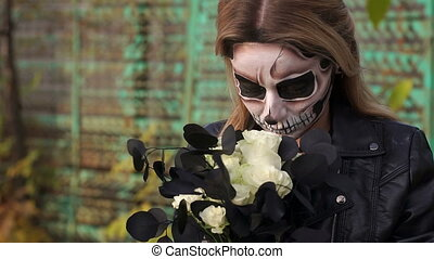 Creepy bride with a bouquet of black flowers and make-up in the form of a skull.