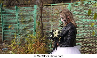 Creepy bride with a bouquet of black flowers and make-up in the form of a skull