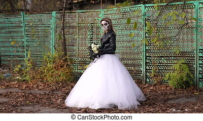 Creepy bride with makeup in the form of skull on the background of an old fence.
