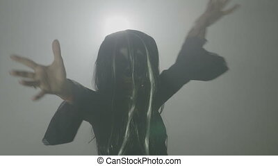Creepy evil female zombie witch wearing a wig and a...