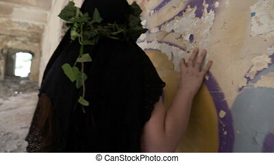 Creepy gothic girl touching and listening the wall in a...