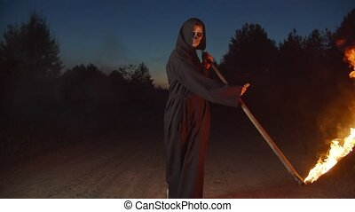 Creepy dark angel of death, grim reaper walking on dirt road in countryside, mowing with burning scythe at night , showing ruthlessness, horror and fear while haunting on halloween holiday.