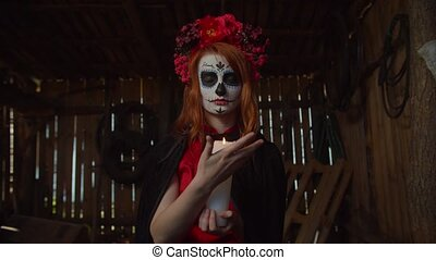 Creepy mysterious our lady of holy death, santa muerte with sugar skull and wreath, gesturing and putting out burning candle as symbol of human soul and safe departure of deceased to afterlife.