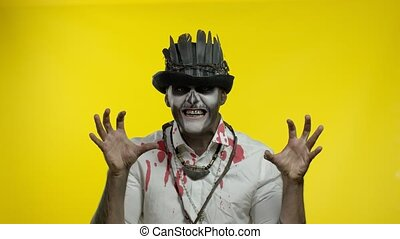 Creepy man with horrible cosplay skeleton makeup in costume with top-hat appears from bottom side, looking at camera, trying to scare. Halloween thematic party. Yellow background. 6k downscale