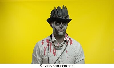 Creepy man with horrible Halloween skeleton makeup in costume with top-hat looking disappointed, upset, sad and crying. Horror theme. Day of The Dead. Isolated on black background. 6k downscale