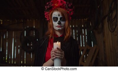 Creepy mysterious santa muerte with sugar skull and colorful wreath wearing black cape, holding burning candle as symbol of human soul, praying for healing and protection in rustic shed.